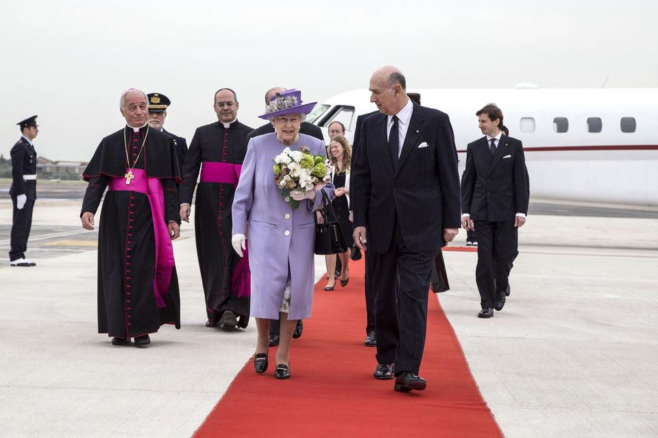 Die Queen wirkt entspannt und gut gelaunt, als sie über den roten Teppich am Ciampino-Flughafen in Rom schreitet.