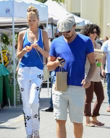 Im Partnerlook: Toni Garrn und Leonardo DiCaprio haben sich für ein blaues Oberteil und eine helle Hose entschieden, um über den Wochenmarkt zu bummeln. Auch ihr Blick aufs Telefon wirkt, als wäre er abgesprochen.