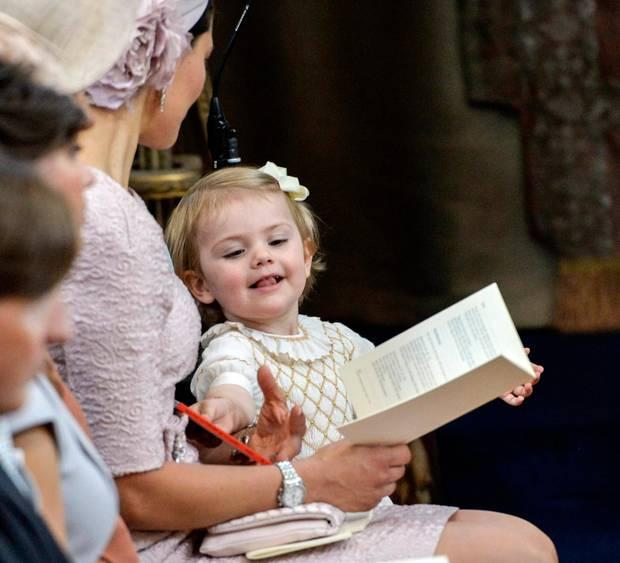 Estelle, auf einem eigenen Ministuhl, hat schon das Gottesdienstprogramm angeschaut und möchte nun ihr Bilderbuch.