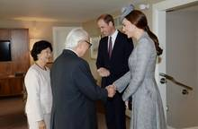 """""""Telegraph.co.uk"""" zufolge stammt Herzogin Catherine silberner Mantel vom Desginerlaber Alexander McQueen und der Fascinator von Jane Taylor. Ihr Haar trägt die Herzogin zu einem tiefen Zopf gebunden."""