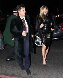 Supermodel Kate Moss trägt ein hautenges, schwarzes Latex-Kleid von Atsuko Kudo, zu dem sie eine voluminöse Fake-Fur-Jacke stylt.