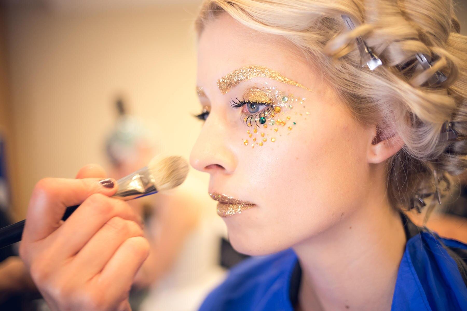 """Auf der """"Mercedes-Benz Fashion Week Berlin"""" zeigt Lena Gercke als neue Botschafterin für """"Maybelline New York"""" ihre Bandbreite als Beauty- und Fashion-Model auf dem Laufsteg: Hier wird sie gerade mit dem effektvollen Gold-Look geschminkt."""