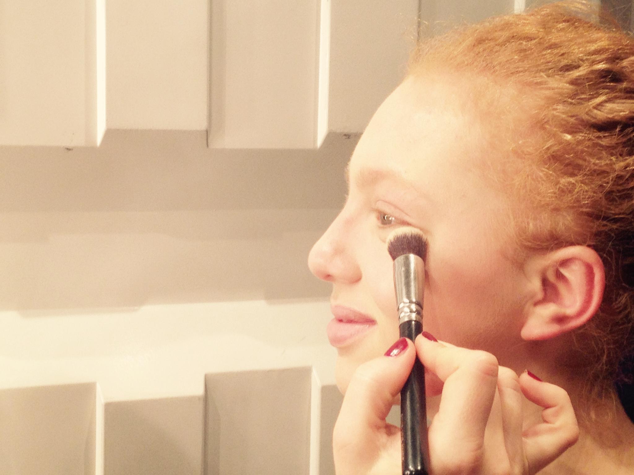 Angela Ermakova wird vor der Show von Riani geschminkt.