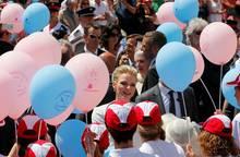 Die vielen Schaulustigen, die gratulieren wollen, schwenken bunte Balllons.