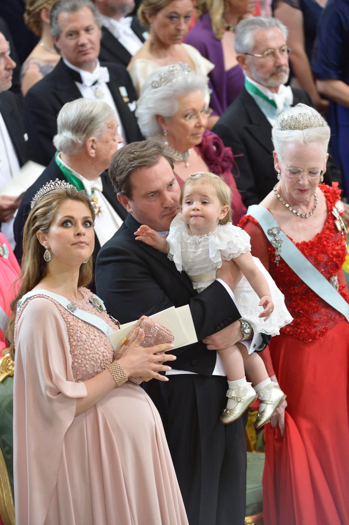 Prinzessin Leonore, mit Schnuller, sitzt mal bei ihren Eltern auf dem Schoss, mal bei Großmutter Silvia oder Onkel Daniel.