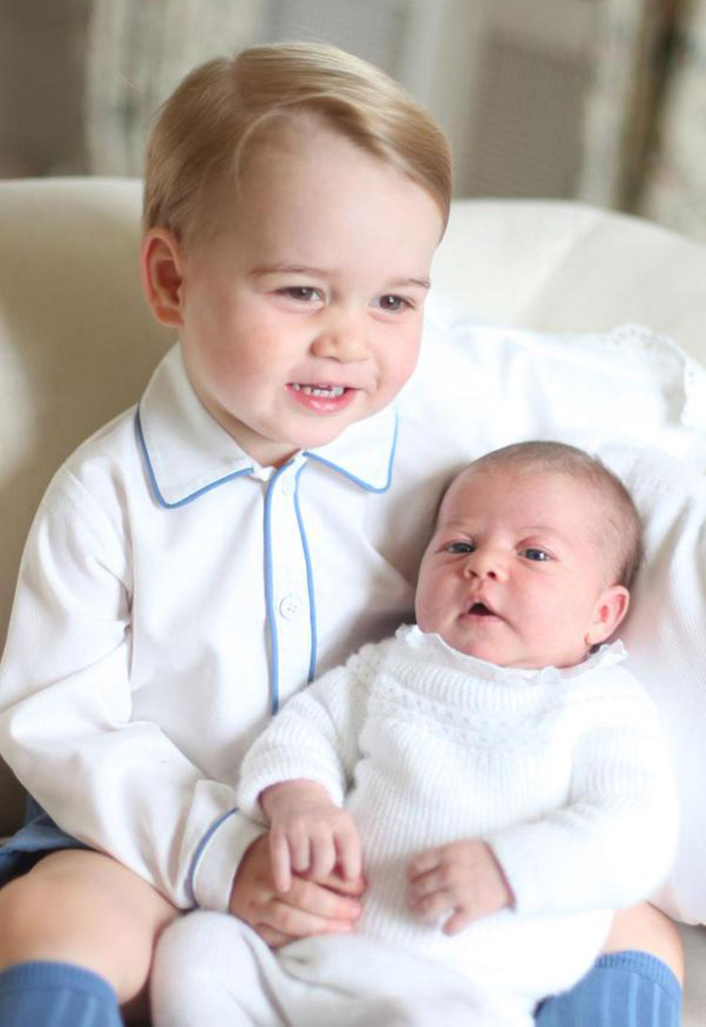 Prinz George der lachende Trendsetter: Er trägt zum ersten Geschwister-Fotoshooting blaue Strümpfe, eine blaue Hose und ein Hemd mit blauem Streifen - sehr stylish!