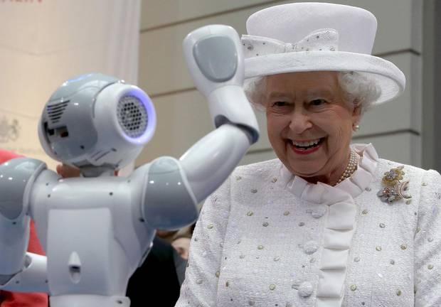 Dass der Roboter ihr auf Kommando zuwinkt, amüsiert die Queen offenbar.