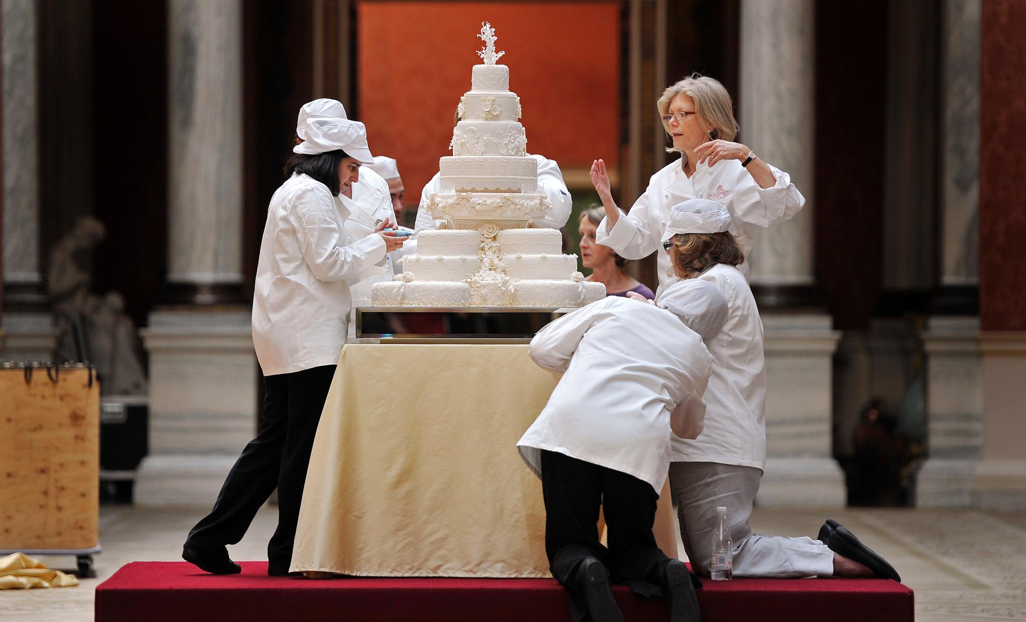 Hier noch einmal die Hochzeitstorte von Prinz William und Herzogin Catherine vom 29. April 2011 im Gesamtbild. So bekommt man eine Ahnung von der Größe dieses 17-Torten-Kunstwerks. Die Dame mit dem blonden Haar, die da von rechts dirigiert, ist die berühmte Konditorin Fiona Cairns, die Urheberin der Leckerei.