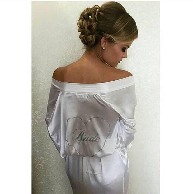 """Kate trägt an ihrer Hochzeit eine wunderschöne Hochsteckfrisur. Ihr weißer Morgenmantel trägt am Rücken die Aufschrift """"Bride"""" (Braut)."""
