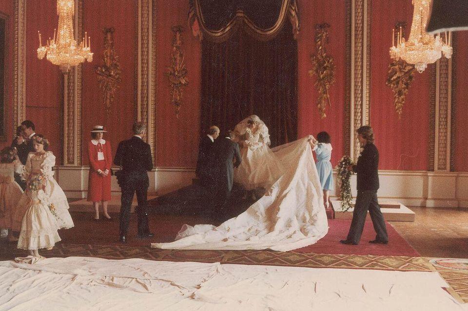 Prinzessin Dianas Brautkleid von der Designerin Elizabeth Emanuel wird für ein offizielles Hochzeitsfoto drapiert. Dafür musste die acht Meter lange Schleppe aus englische Seide in Position gebracht werden
