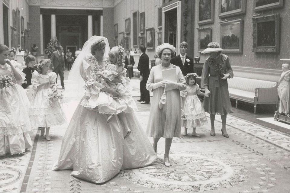 Prinzessin Diana trägt eines ihrer Blumenmädchen auf dem Arm und spricht ihr Mut zu
