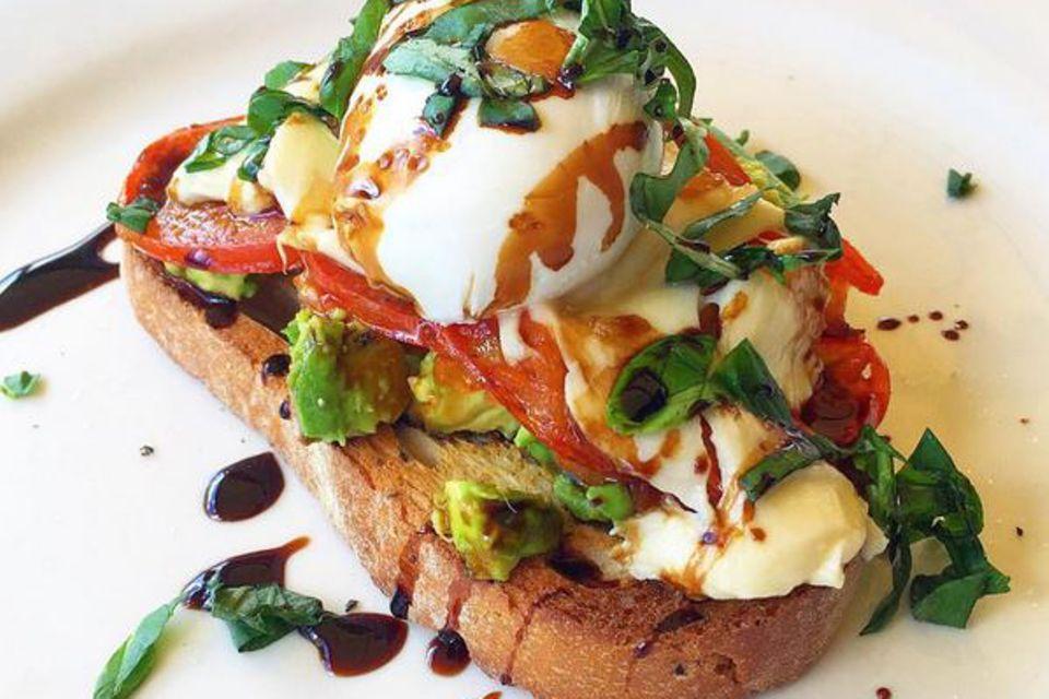 Yummi! Zum Frühstück gibt es bei Kayla Itsines ein Vollkorntoast mit pochiertem Ei, Avocado, Tomaten und Basilikum.