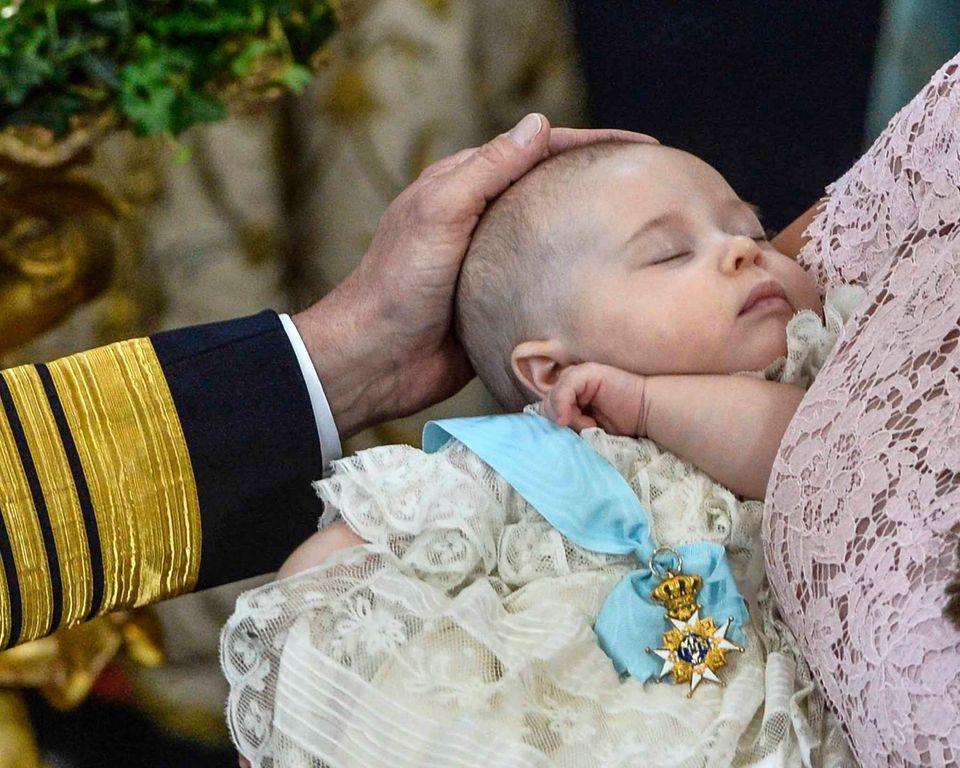 Liebevoll streicht König Carl Gustaf seiner jüngsten Enkelin, die weiter friedlich schlummert, über den Kopf.