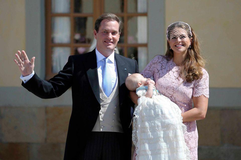 """Die Eltern zeigen sich mit dem Täufling den vielen Schaulustigen, die bei strahlendem Sonnenschein gewartet haben.  Prinzessin Madeleine trägt ein Kleid in zartem rosé mit Spitze aus dem Hause """"Valentino""""."""