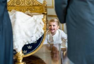 Prinzessin Estelle amüsiert sich und spielt hinter der goldenen Wiege.