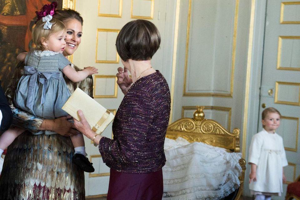 Im Hintergrund schaut Prinzessin Estelle zu, wie Prinzessin Madeleine, Chris O'Neill und (nicht im Bild) König Carl Gustaf und Königin Silvia die Glückwünsche entgegen nehmen. Cousine Leonore ist ebenfalls dabei.