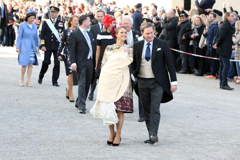 Die Taufgesellschaft, angeführt von Prinzessin Madeleine mit ihrem Sohn auf dem Arm und Ehemann Chris an ihrer Seite, schreitet zum Empfang.