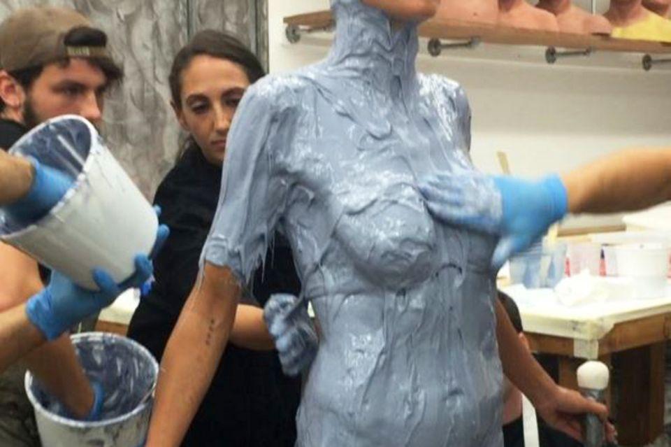 """""""Schleimt mich ein"""" - Heidi Klum wird von ihrem Team von Kopf bis Fuß in mit blauer Gips-Masse bestrichen."""