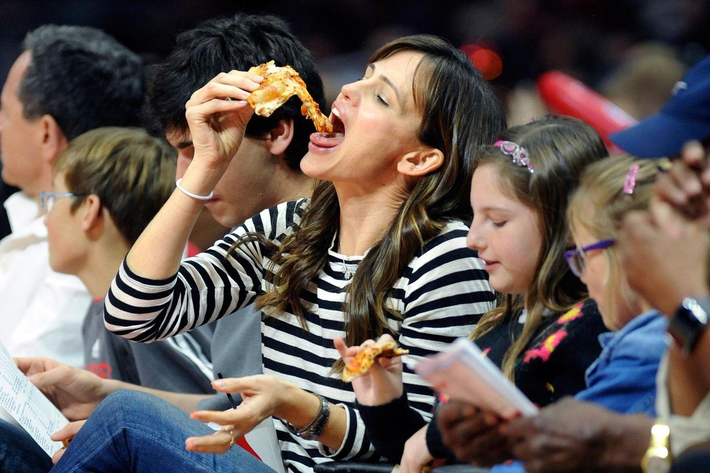Wie es sich zu einem spannenden Basketballspiel gehört, isst Jennifer Garner genüsslich ein Stück Pizza und fiebert in der Halle mit.