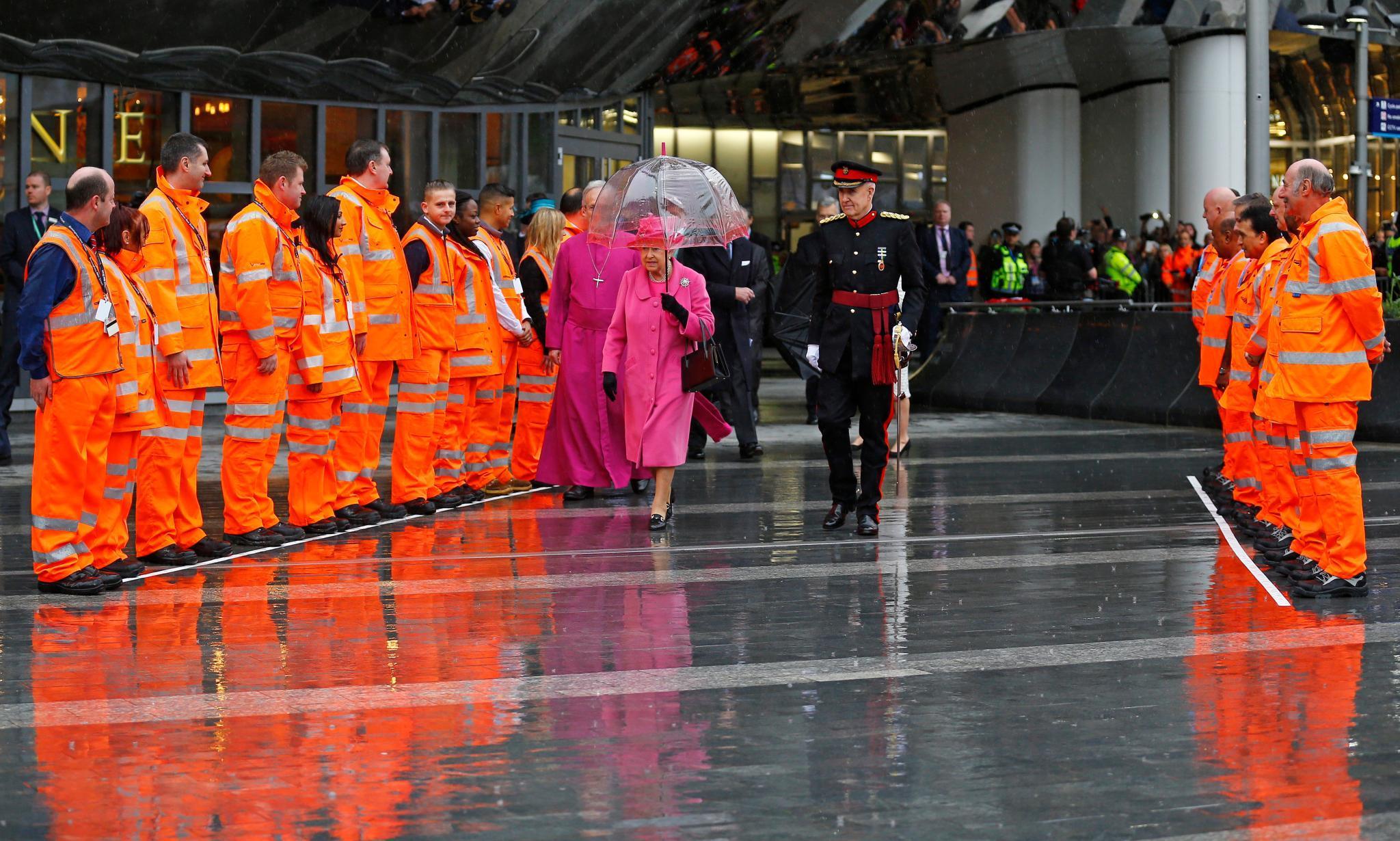 Die Queen kommt in einem pinken Mantel nach Birmingham, dessen leuchtende Farbe besonders stark auffällt, als sie von den Metro-Mitarbeitern umgeben ist.