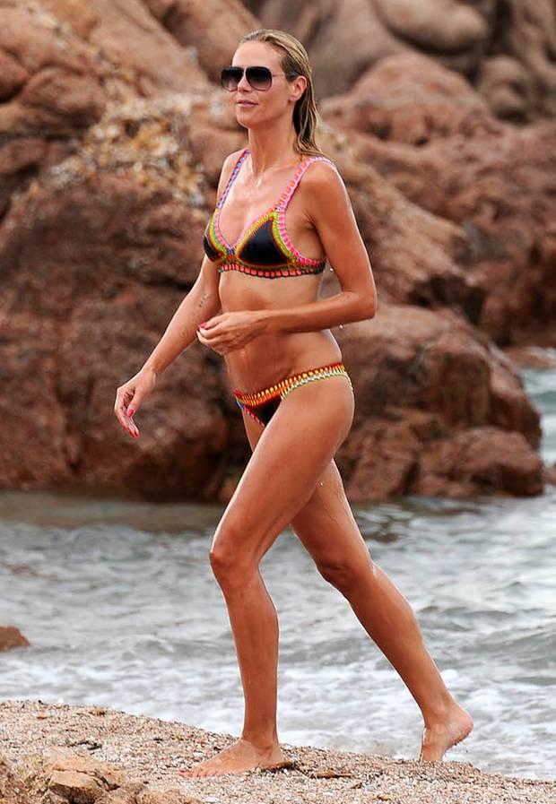 Super-Body braucht Super-Bikini: Heidi Klum entsteigt in ihrem schwarzen Kiini-Entwurf mit knalligen Farbakzenten dem Meer.