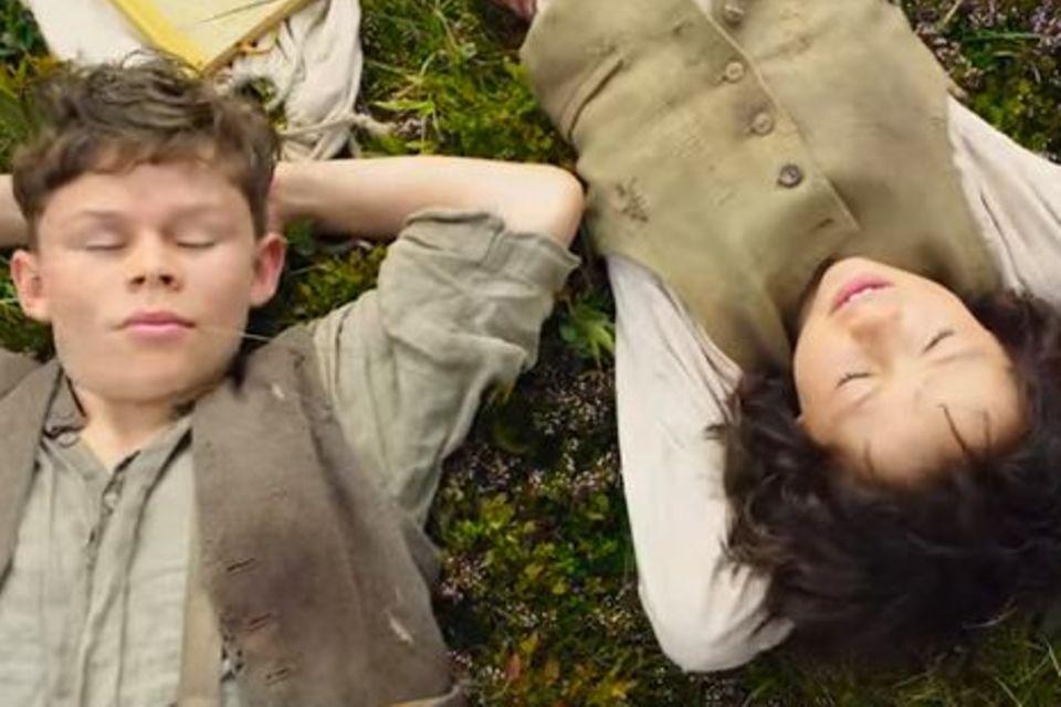 Szene aus der Neuverfilmung: Heidi und Peter machen eine Pause in den Bergen.