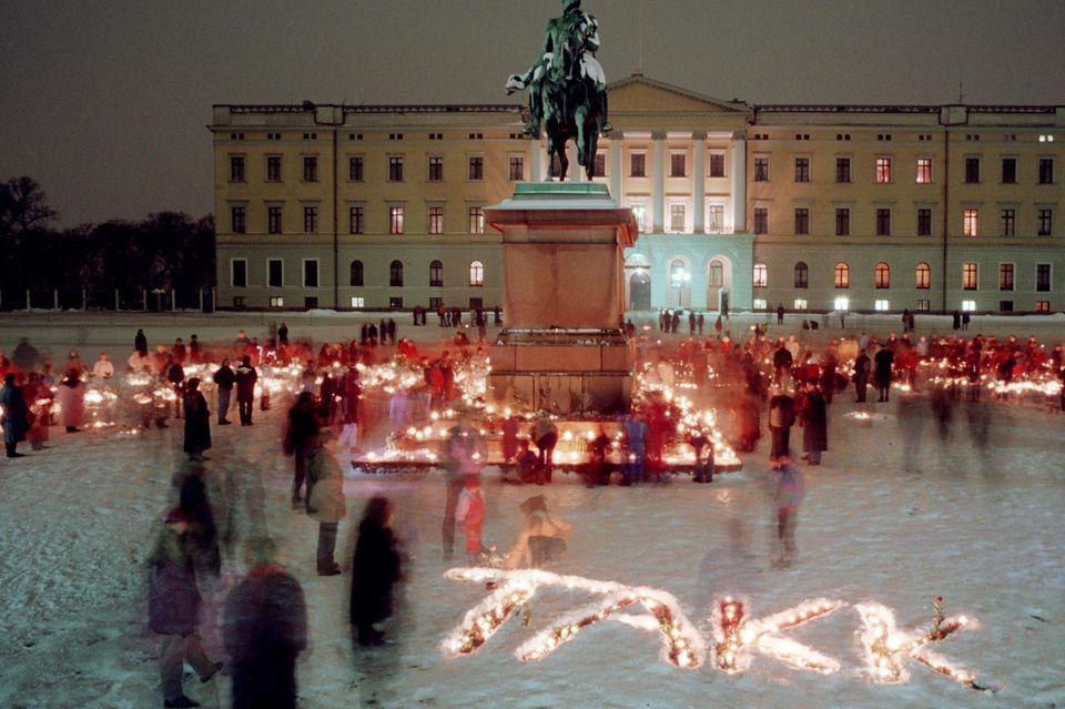 """So eindrucksvoll verabschiedeten die Norweger sich damals, 1991, von ihrem verstorbenen König Olav: Trotz der Kälte dieser Januarnacht strömten sie mit Kerzen in den Händen vor das Stadtschloss in Oslo und formten mit diesen Kerzen das Wort """"Takk"""" (Danke) auf dem Boden. Ein unvergessenes Bild."""