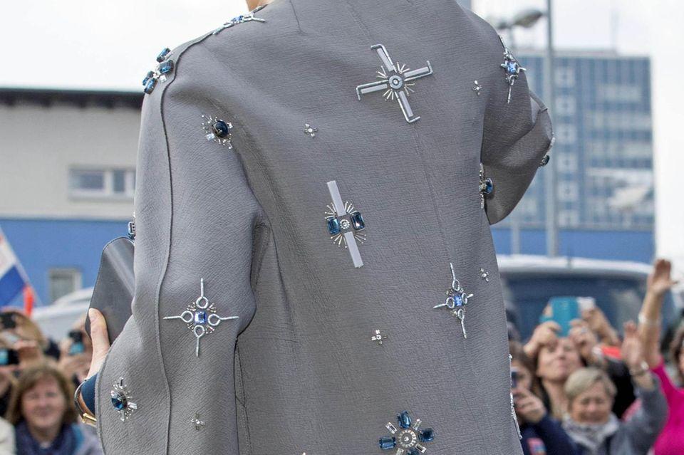 Schmucksteine, Schrauben und Nägel zieren den Mantel von Königin Máxima. Wer will, kann in einigen Elementen Anlehnungen an das Hakenkreuz-Symbol erkennen.