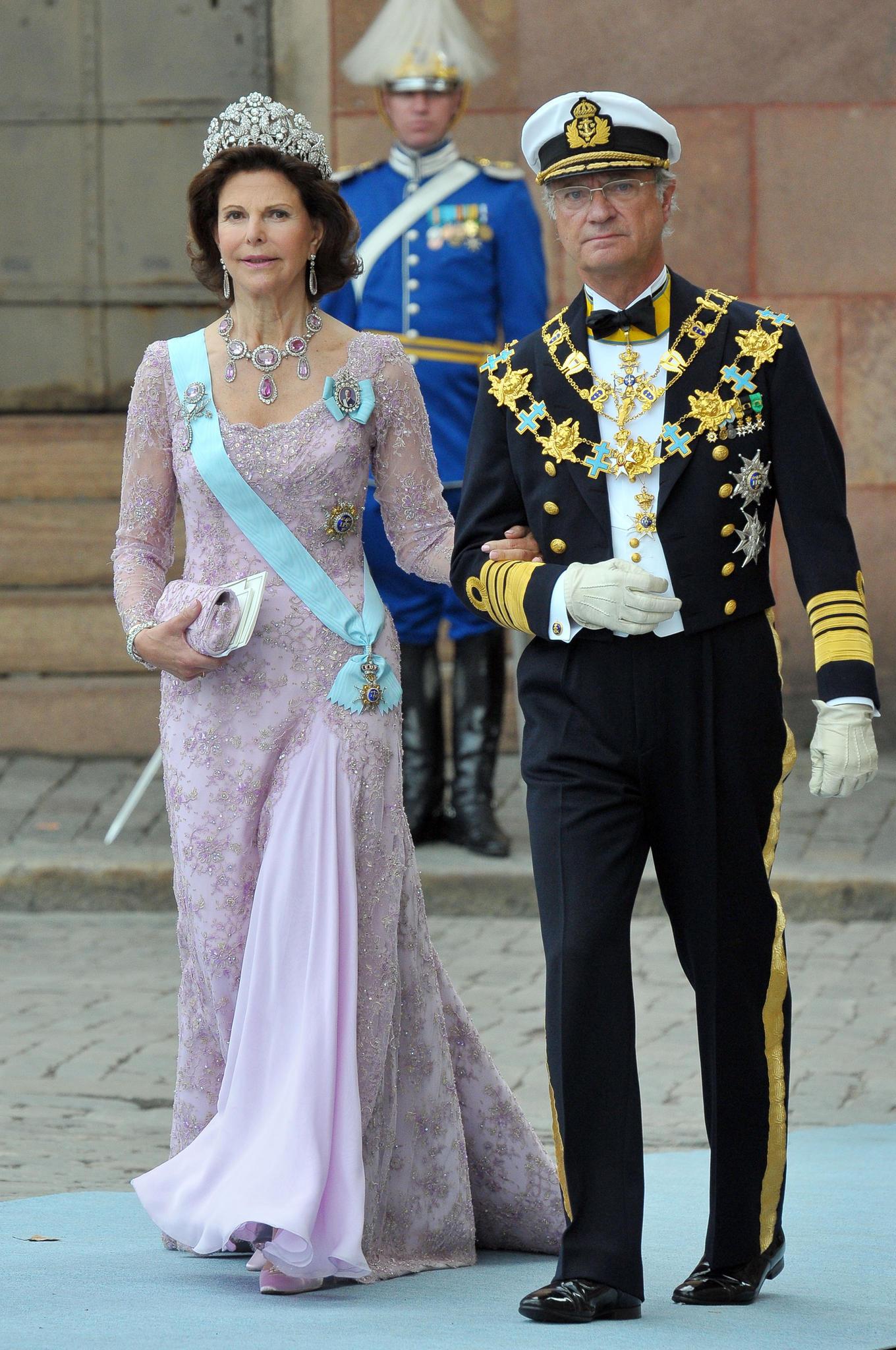 """2010  Königin Silvia bemüht sich Haltung zu bewahren, aber böse Gerüchte versuchen das Königspaar zu entzweien. Zunächst sorgt das umstrittene Skandalbuch """"Der widerwillige Monarch"""" für Aufruhr. Darin ist von wilden Festen in Stripclubs und einer Affäre die Rede, die Carl Gustaf mit der Sängerin der Band """"Army of Love"""" gehabt haben soll. Silvia steht aber hinter ihrem Mann und lächeltdie Gerüchte beiseite."""