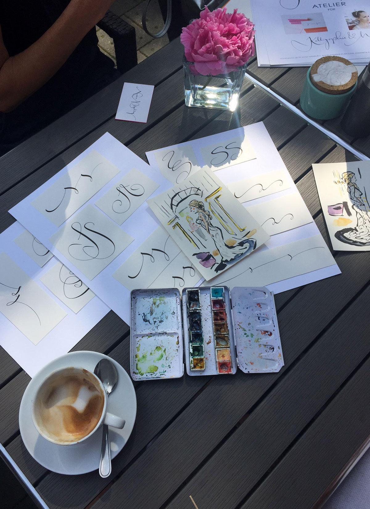 """Bei einem Cappucino lässt sich Kolumnistin Sue von der Hochzeitsplanerin Nadine Metgenburg von """"Fine Weddings"""" Illustrationen und Kalligrafie-Vorschläge für das perfekte Hochzeitsfest zeigen."""