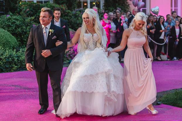 Von ihrem Stiefvater Peter und ihrer Schwester Jenny wir Daniela Katzenberger den pinken Teppich entlang geführt und gibt dabei den Blick auf ihr mit 20.000 Perlen besticktes und über elf Kilo schweres Hochzeitskleid frei.