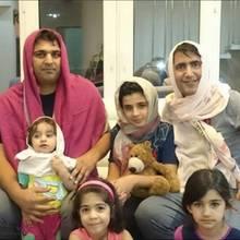 Männer mit Kopftüchern und ihrer Familie.
