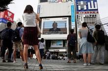 In Tokio stoppen Menschen im Vorbeigehen und hören dem Kaiser und seiner Ansprache zu.