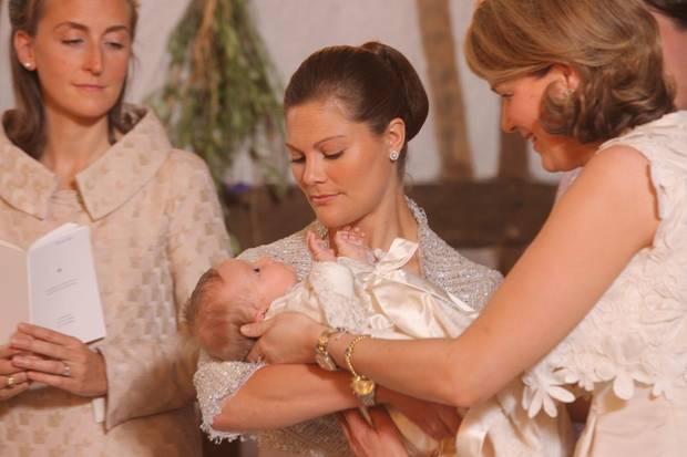 2008 waltet Prinzessin Victoria ihres Amtes in Belgien: Bei der Taufe von Prinzessin Eléonore hält sie ihre Patentochter über das Taufbecken.