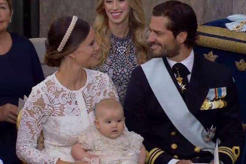Prinz Alexander schaut erstaunt umher, seine Eltern werfen sich innige Blicke zu.