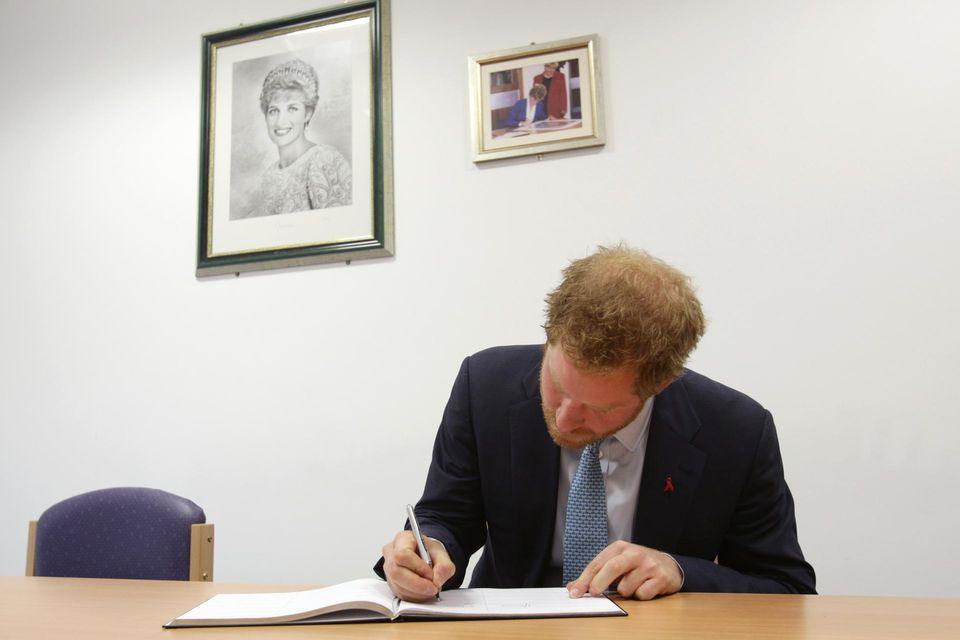 Bei seinem (offiziellen) Besuch im Dezember 2015 trägt sich Prinz Harry in Mildmay ins Gästebuch ein. An der Wand erinnern Bilder an seine verstorbene Mutter Diana.