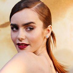 Die geglätteten Haare streng gescheitelt und am Hinterkopf zusammengebunden: So gestylt zeigt sich Lily Collins bei einer Premiere in Hollywood.