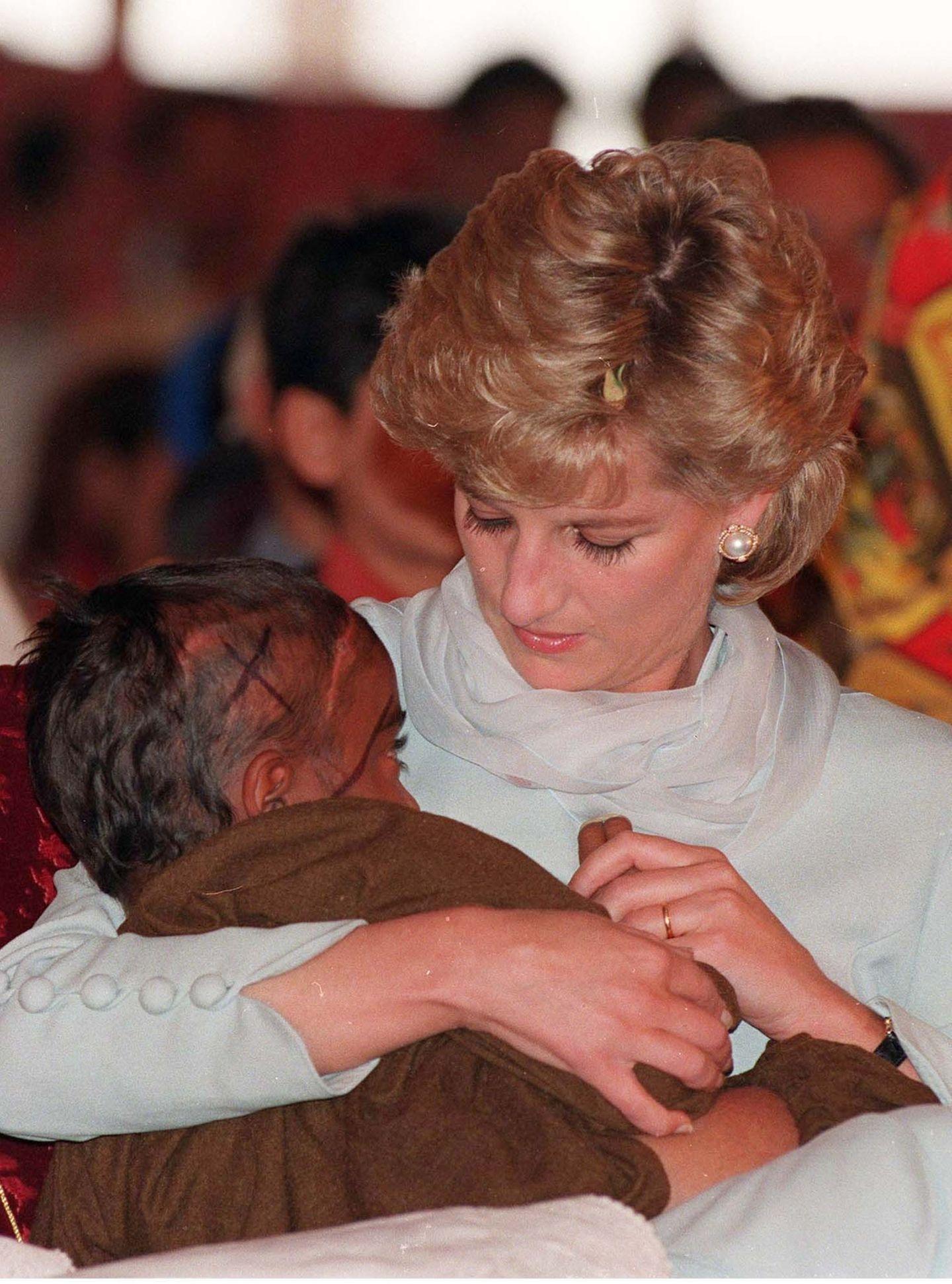 1996   Keine Scheu vor Krankheit: Diana tröstet hier ein krebskrankes Kind während eine Besuch in Lahore, Pakistan.