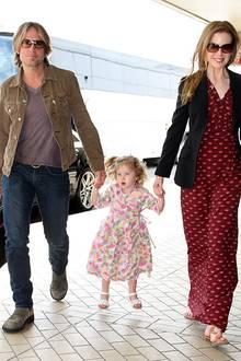 23. Dezember 2010: Keith Urban und Nicole Kidman nehmen ihre Tochter Sunday Rose am Flughafen in Sydney in ihre Mitte.
