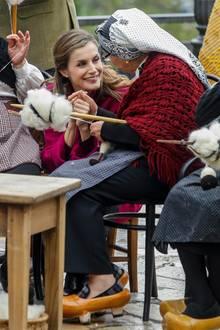 Königin Letizia lässt sich von einer alten Dame im Weben einweisen.