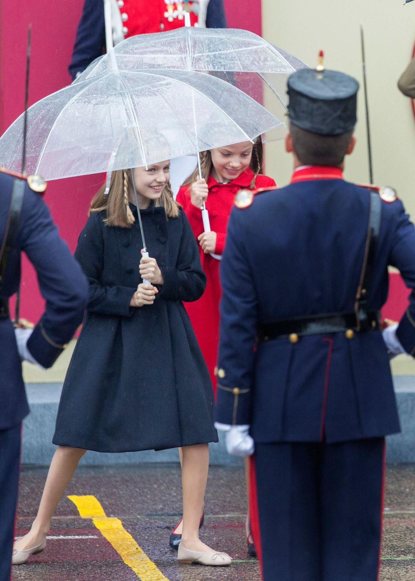 Regen, was soll's! Prinzessin Leonor und Prinzessin Sofia haben am spanischen Nationalfeiertag auch unter ihren Regenschirmen mächtig Spaß!