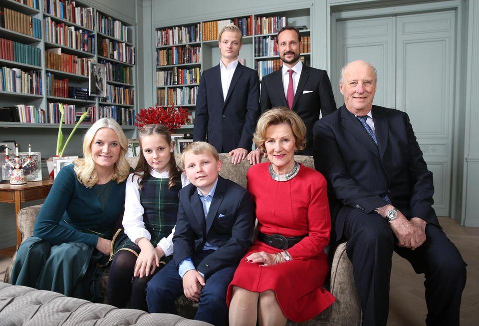 Das offizielle Gruppenfoto der norwegischen Königsfamilie vor dem Weihnachtsbaum im Wohnzimmer von Gut Skaugum: (unten) Prinzessin Mette-Marit, Prinzessin Ingrid Alexandra, Prinz Sverre, Königin Sonja. Oben stehen Marius Borg, Prinz Haakon und König Harald, der in einem Monat sein 25-jähriges Thronjubiläum feiert.