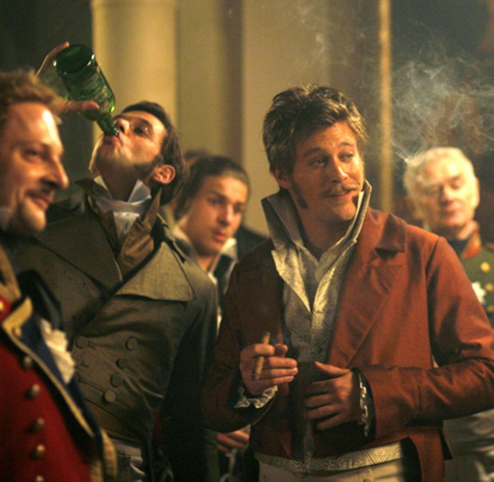 Pierre (Alexander Beyer, l.) lässt sich zu einem Trinkgelage mit Anatol (Ken Duken, r.) und anderen Freunden hinreißen