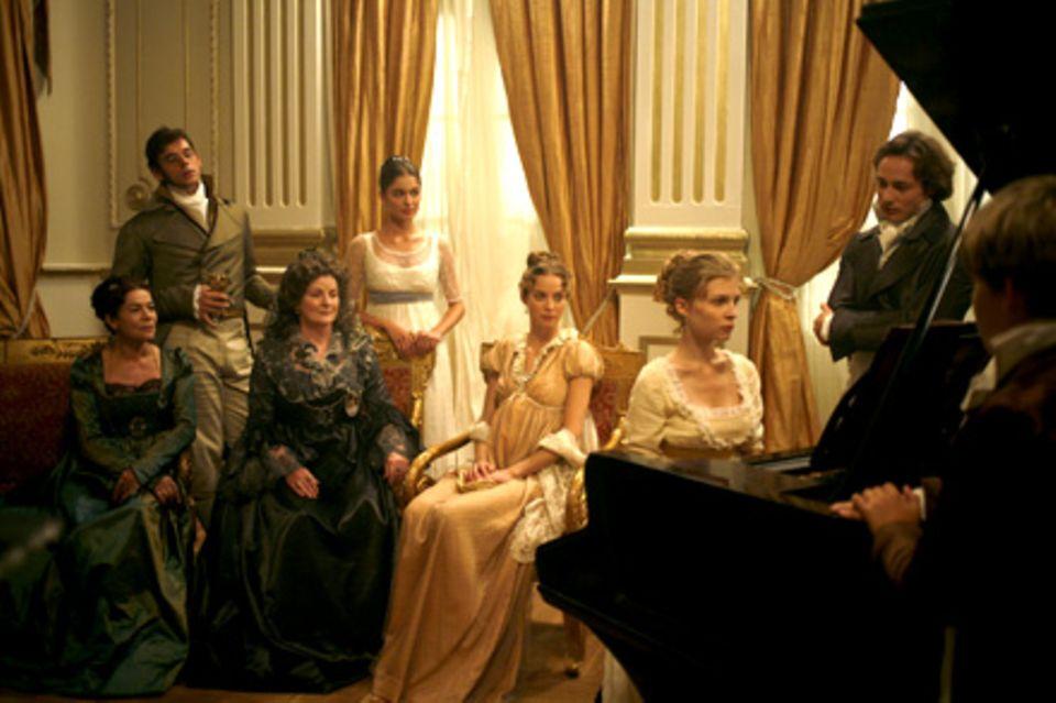 Natascha (Clémence Poésy, 2.v.r.) spielt den Gästen der Familie auf dem Klavier vor. V.l.n.r.: Gräfin Rostowa (Hannelore Elsner)