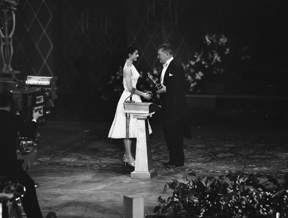"""1954: Audrey Hepburn bekommt ihren Oscar für """"Ein Herz und eine Krone"""" von Gastgeber Jean Hersholt überreicht."""