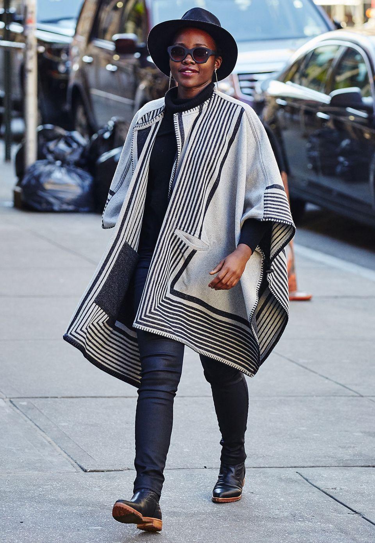 Lupita Nyong'o hüllt sich zum Schutz gegen die Kälte in ein schwarz-weißes Cape im Ethno-Style und trägt damit das Trendteil der diesjährigen Herbst/Winter-Saison.