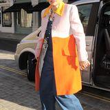 Colour-Blocking auf höchstem Niveau: Rita Ora kombiniert ihren farbenfrohen Mantel zu einem schicken Hut und achtet darauf, dass sie dabei bei warmen Tönen bleibt.