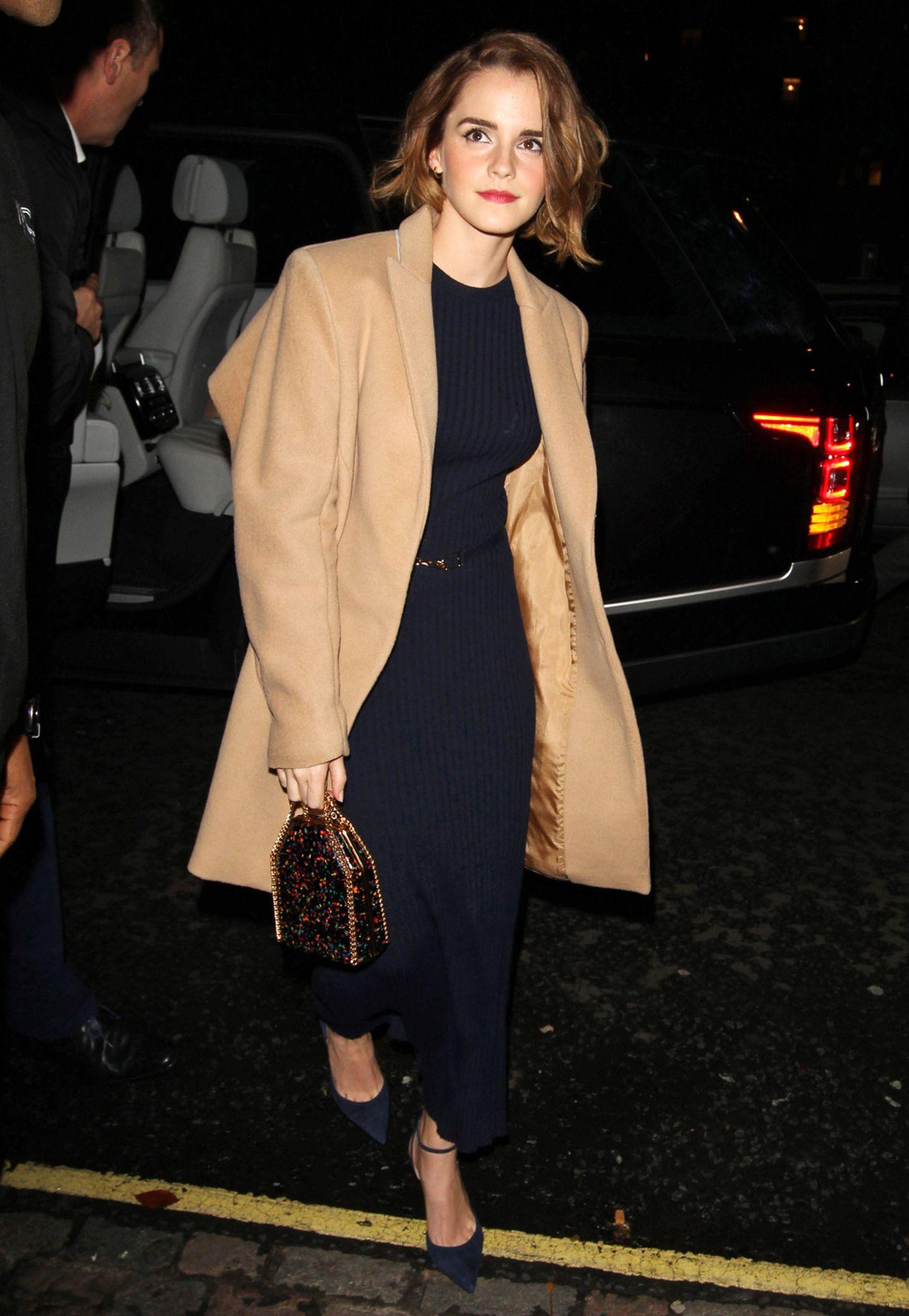 Auch Emma Watson mag auf den Mantel-Klassiker nicht verzichten. Sie trägt ihn zum dunkelblauen Wollripp-Kleid.