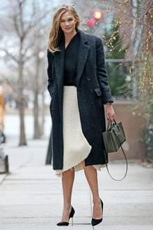 Flauschig und sehr trendy ist der schwarze Mantel von Supermodel Karlie Kloss, den sie elegant zu Midi-Rock und Pullover stylt.