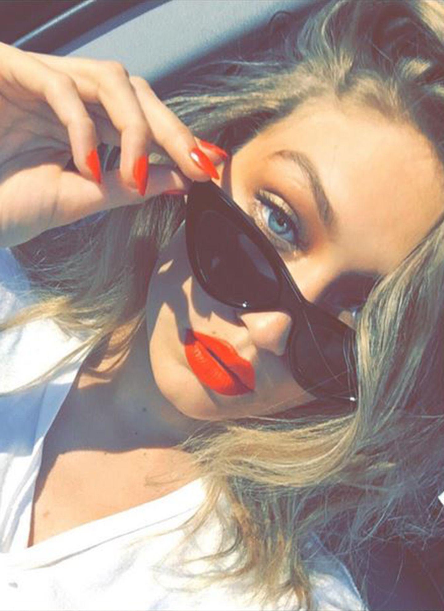 Wow, was für ein Diva-Look! Gigi Hadid rundet den Look rund um ihre Cateye-Sonnenbrille mit knallrotem Lippenstift und farblich passendem Nagellack ab.